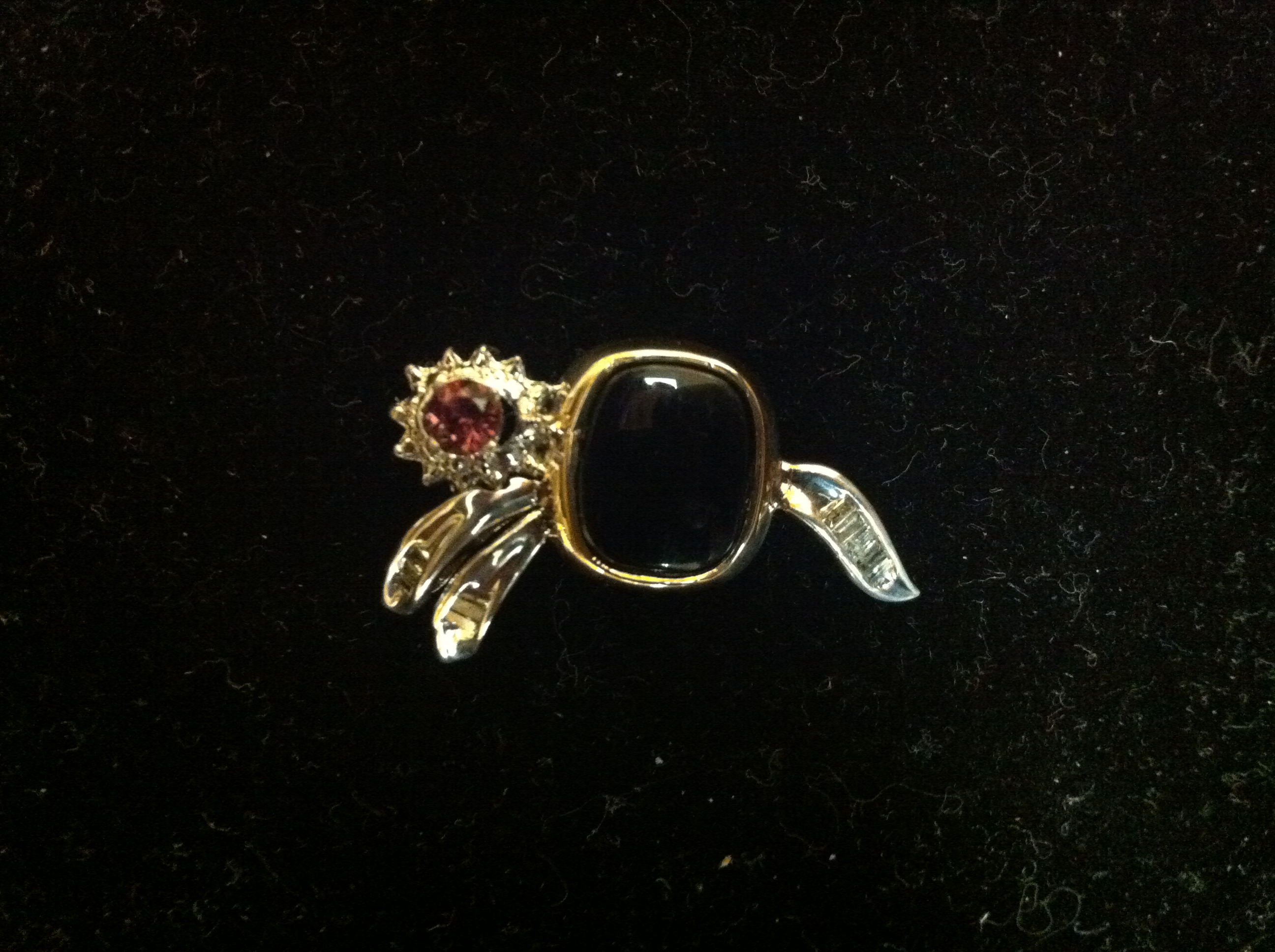A gold pin with a black stone and a red stone