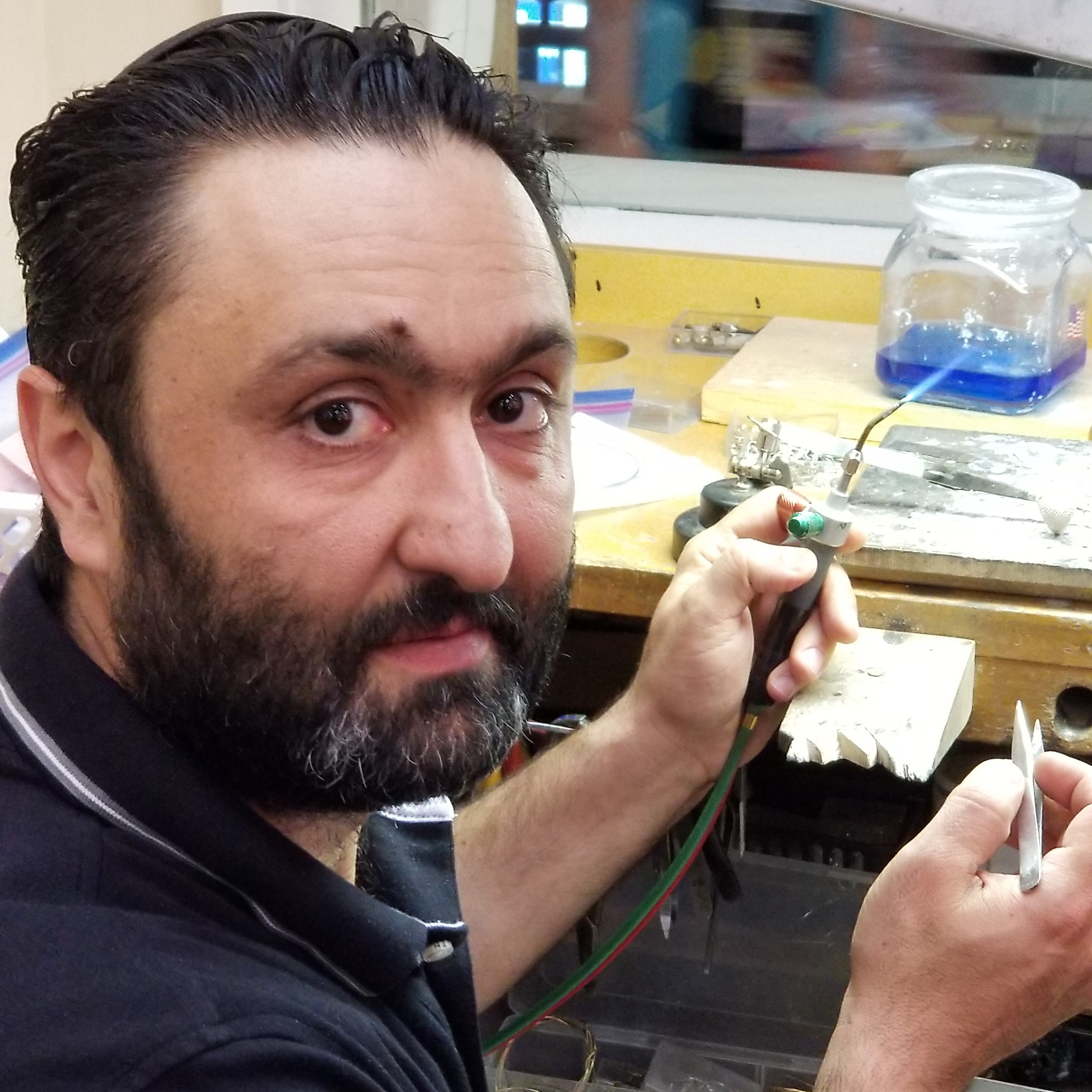 Michael Gadelov holds a jewelry torch and a pair of tweezers to complete a job at his Jewelers Bench