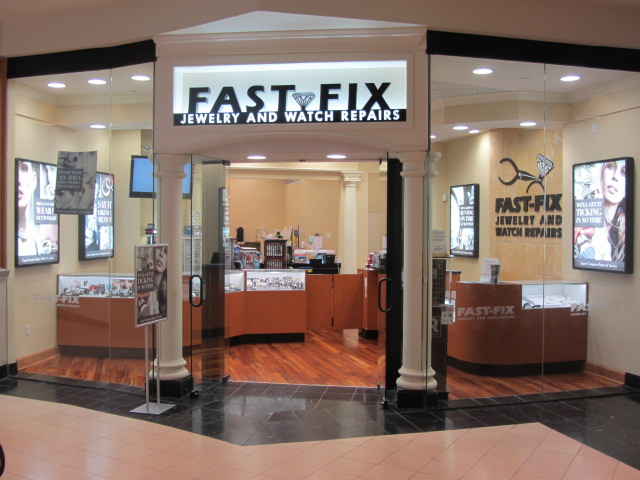 Fast Fix Jewelry and Watch Repairs store front photo at the Perimeter Mall. Showing a glass store front with two white columns forming the entrance to the store. Fast Fix signage on top of main glass door.