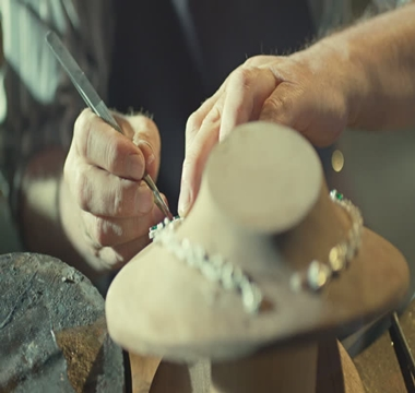 female jeweler hands repairing a pearls necklace