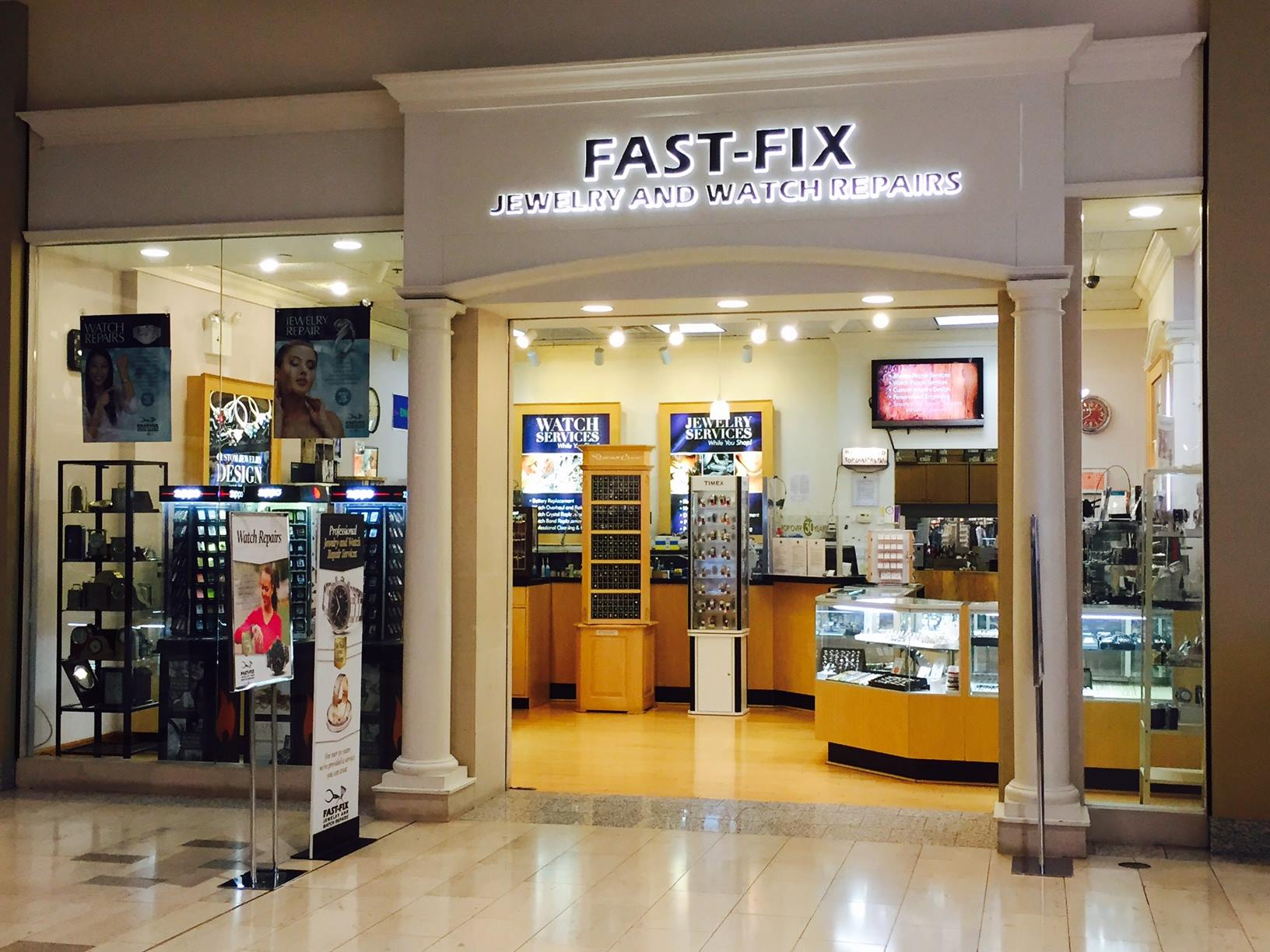 Store front of a Fast Fix Jewelry and Watch Repairs store at Staten Island Mall. Shows 2 white pillars with glass walls showing the interior of the store