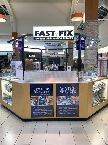 Fast-Fix kiosk in Manassas mall. Hexagonal shape with glass cabinets on the sides and wood center with Jewelry and Watch repair services signs