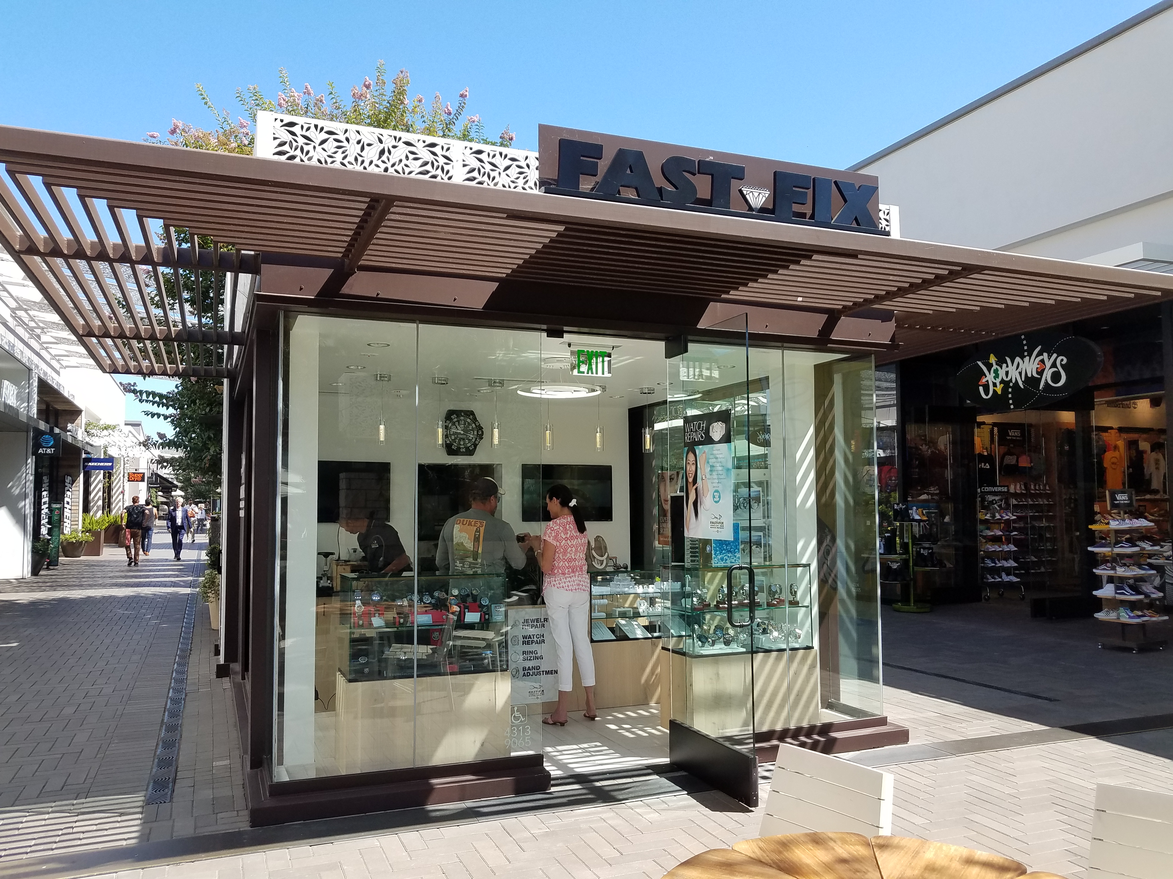 Fast-Fix Jewelry and Watch Repairs kiosk. Picture of its exterior showing a glass front with wood frame and clear view of the front desk and jewelry display.