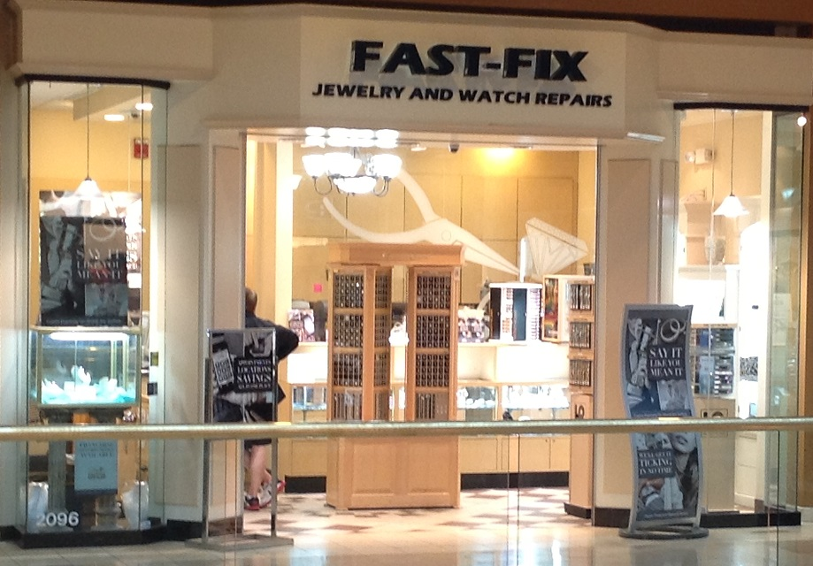 Storefront picture of Fast-Fix Jewelry and Watch Repairs store in Scottsdale, AZ. Front glass with 2 columns forming the entrance and the brand name on the top