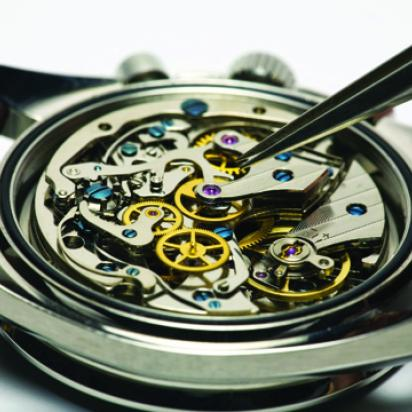 Inside of an automatic watch being repaired with tweezers.