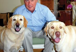 Gerry Weber, Fast-Fix CEO, pictured embracing his 2 rescued golden labs. He is wearing a blue shirt and cream color pants in a living room environment.